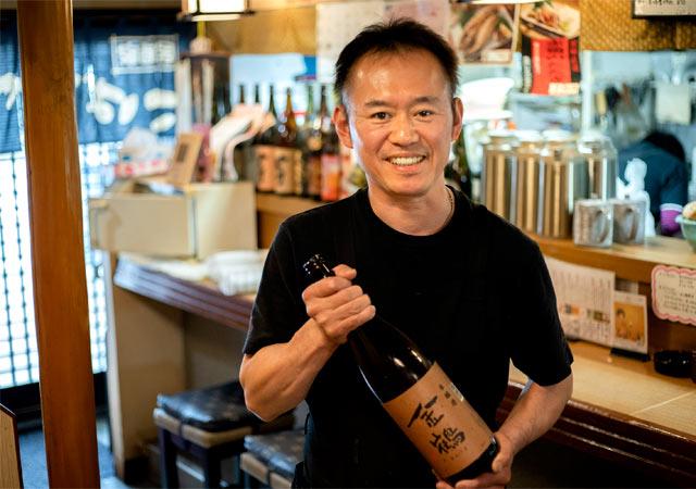 店主の小林伸弘さん。淡麗な飲み口のなかに旨みを感じられる、おすすめの〈金鶴 本醸造〉を持って。
