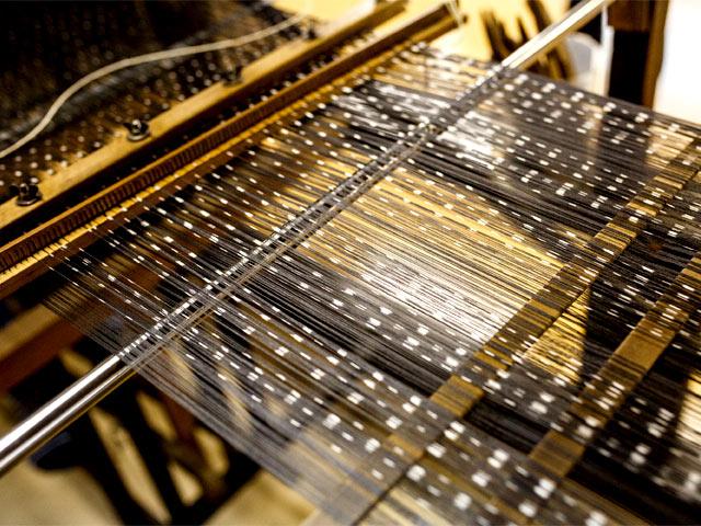織機にとりつけた経糸。白い所がくびりによって防染された部分。