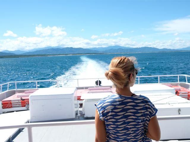 遠のく岩船港と青い海に伸びる白い船跡