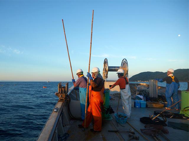 定置網漁船に乗り込んだ10人ほどの漁師たち