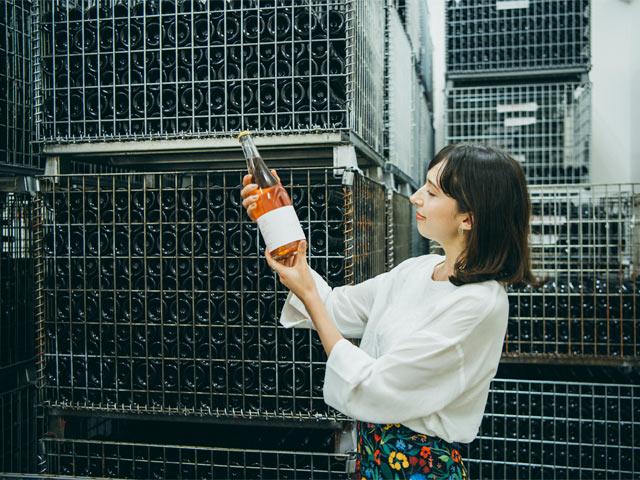 出荷前のボトリングされたワインを手に取るアリスさん。