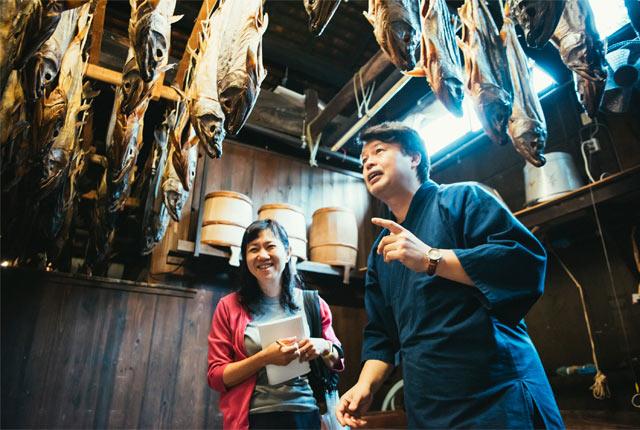 吉川さんから塩引鮭の説明を受ける角田光代さん
