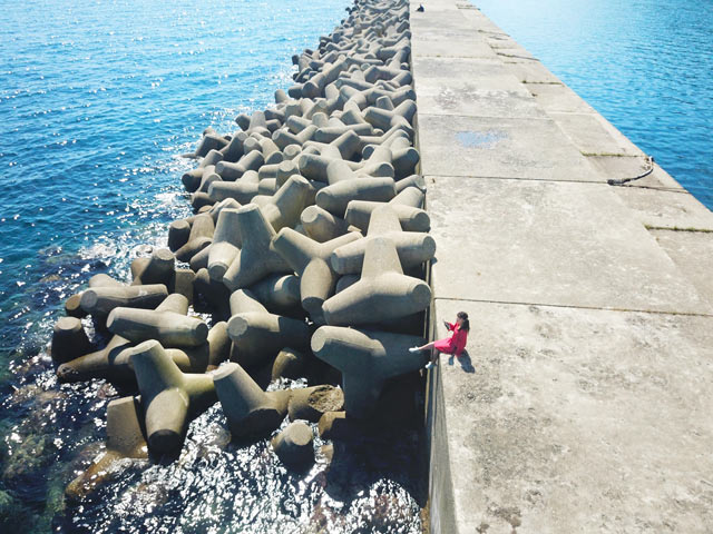 防波堤にすわり海を眺める