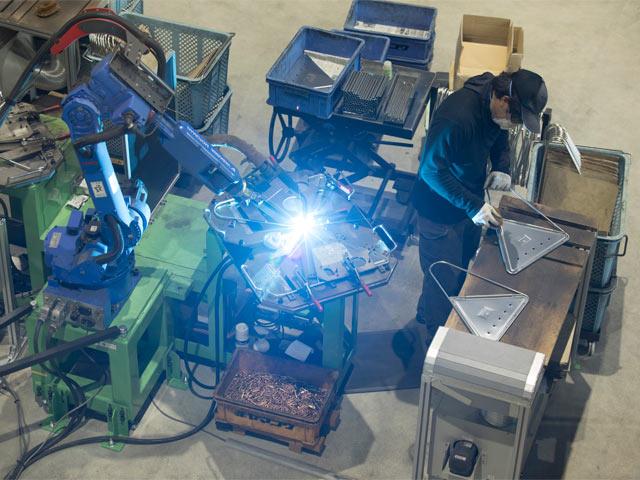 ロボットによる溶接と、溶接で飛び散った火花跡を落とす作業