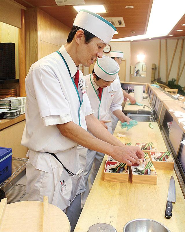 カウンターで寿司を握る職人
