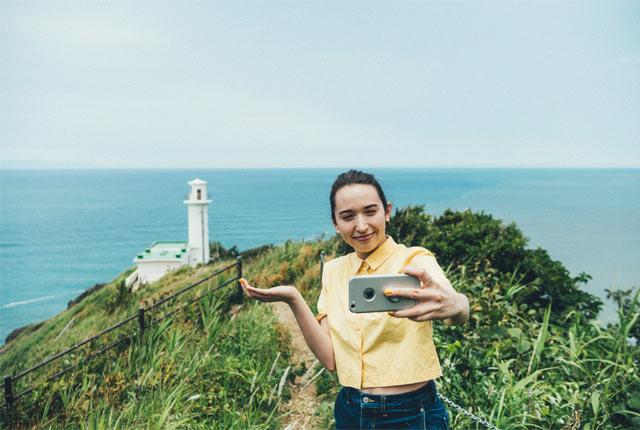 灯台を背景に自撮り中