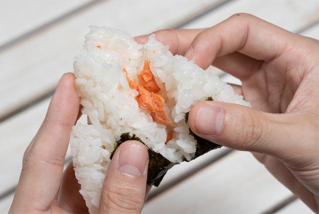 鮭おにぎりを2つに割る