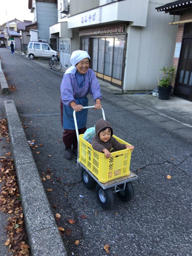 子どもが乗ったカートを押すおばあちゃん