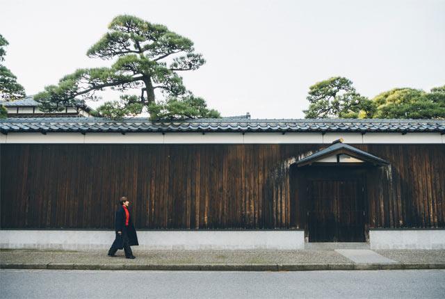 〈旧小澤家住宅〉の塀に沿って歩く坂田さん