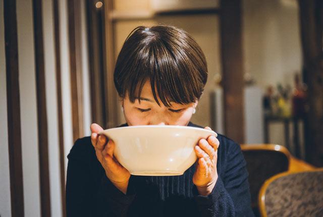 鶏そばのスープを味わう坂田さん