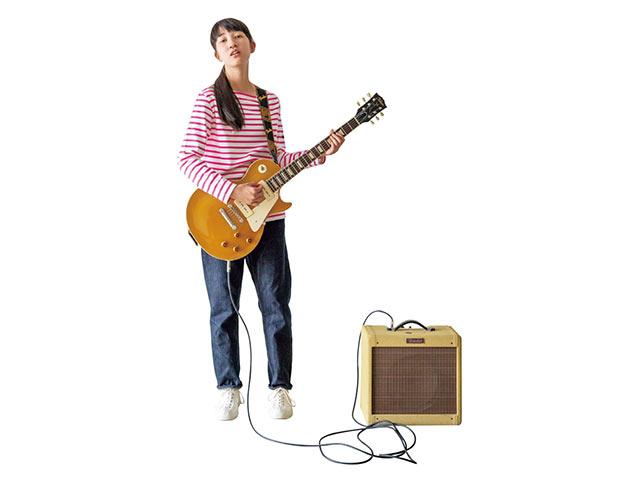 G.F.G.S.のオーダーボーダーを着てギターを弾く女性