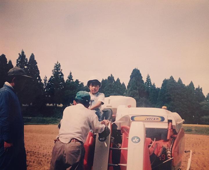 稲刈り機に乗る子どもの頃の横澤夏子さん