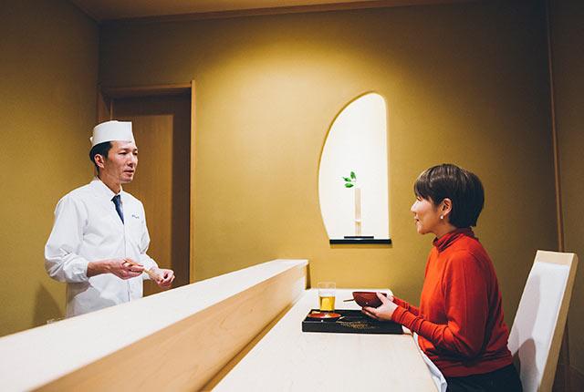 〈鍋茶屋 光琳〉のカウンターに座る坂田阿希子さん
