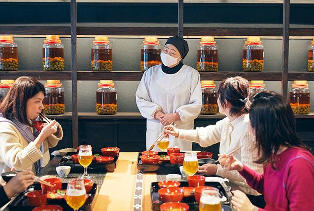 関さんの料理の説明をきくツアー参加者