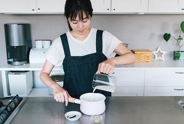 計量カップを使って材料を鍋に入れる
